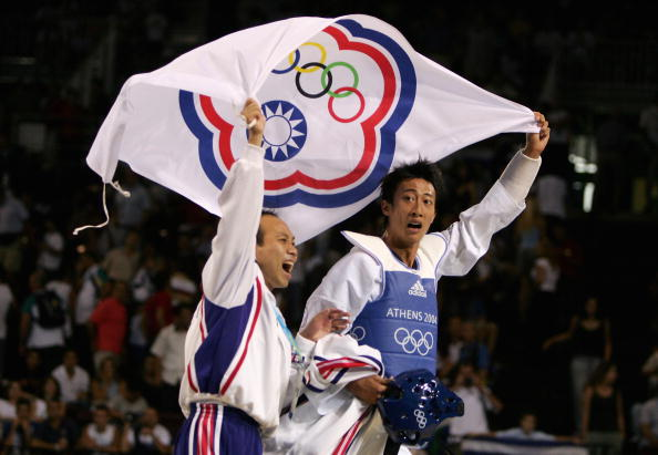 ATHENS - AUGUST 26:  Mu Yen Chu of Chinese Taipei  celebrates with his coach after winning the gold medal with his defeat of Oscar Francisco Salazar Blanco of Mexico in the men's under 58 kg Taekwondo gold medal match on August 26, 2004 during the Athens 2004 Summer Olympic Games at the Sports Pavilion part of the Faliro Coastal Zone Olympic Complex. (Photo by Al Bello/Getty Images)