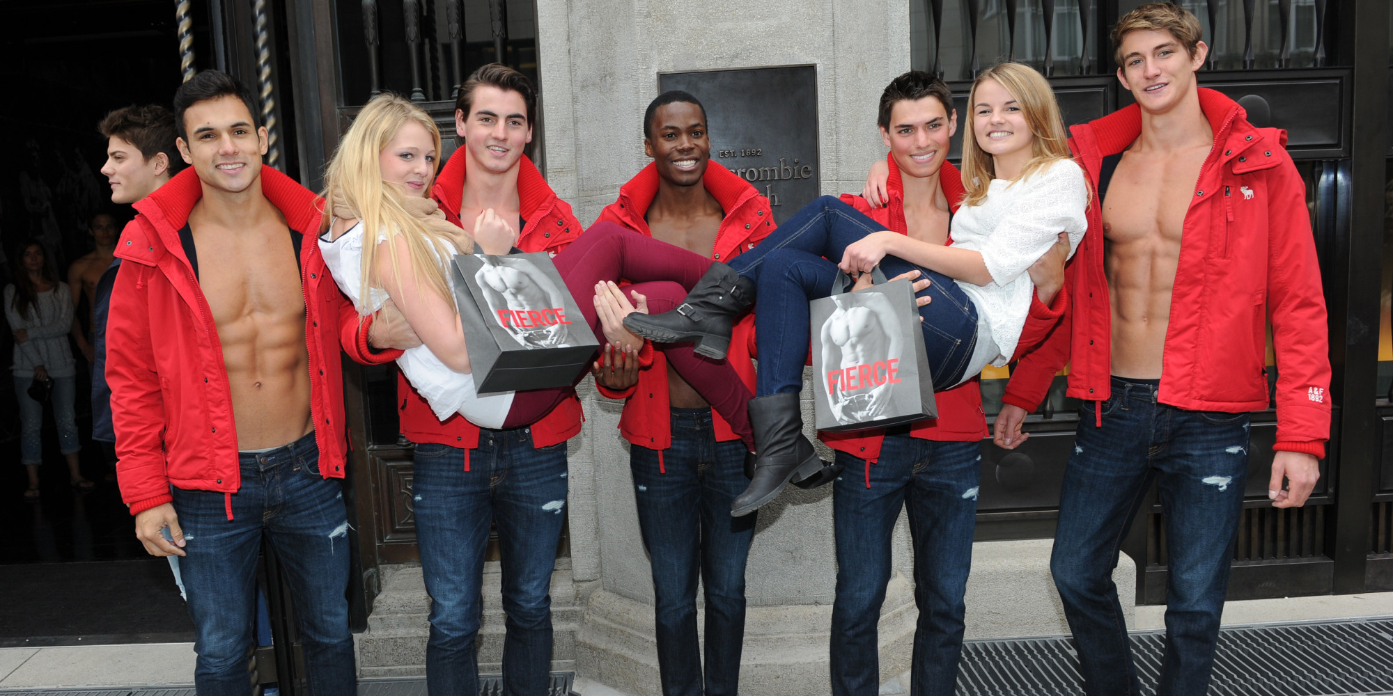 MUNICH, GERMANY - OCTOBER 25:  Young women pose for photographs with male models outside the Abercrombie & Fitch flagship clothing store during the opening of Abercrombie & Fitch Munich flagship store on October 25, 2012 in Munich, Germany.  (Photo by Hannes Magerstaedt/Getty Images)