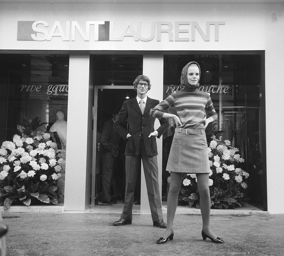 Yves Saint Lauren and Swedish model Ulla in front of his Paris Saint Laurent Rive Gauche boutique.