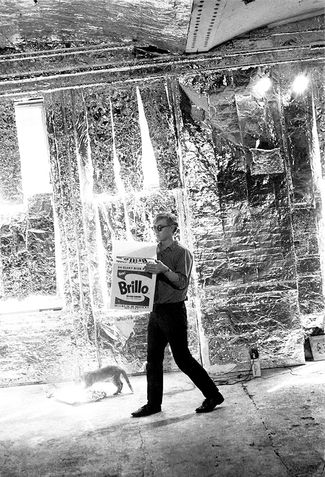 Andy Warhol carrying a Brillo Box sculpture with Billy Name's cat at the Factory.